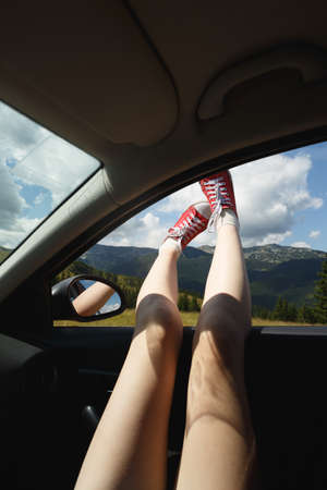 Girl legs in bright sneakers sticking out of the car