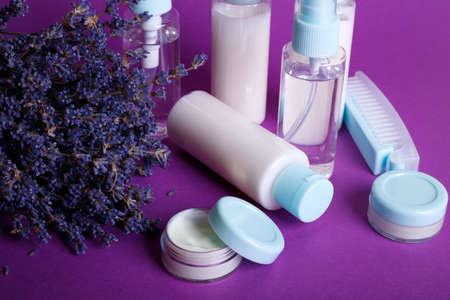 travel beauty kit on a purple background. shampoo, balm, cream, lotion in vials and  lavender Stock Photo