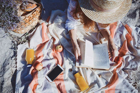 Summer - picnic by the sea. basket for a picnic with with buns, apples and juice. girl on a picnic lies and reads a book Stock Photo