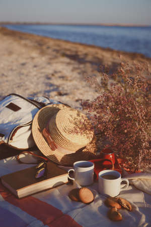 Summer - picnic by the sea. backpack, bouquet, two cups of coffee, cookies, hat, retro camera and book in sunset light