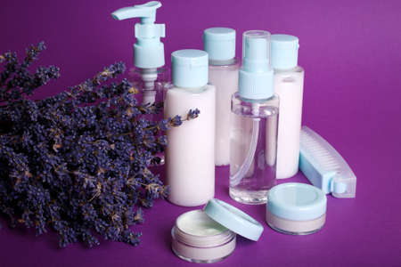 travel beauty kit on a purple background. shampoo, balm, cream and lotion in vials