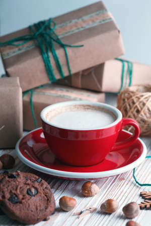 festive mood. Gifts, cup cappuccino and Christmas decor on the wooden background.