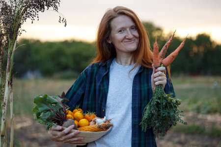 happy girl holds  bowl of vegetables from your garden