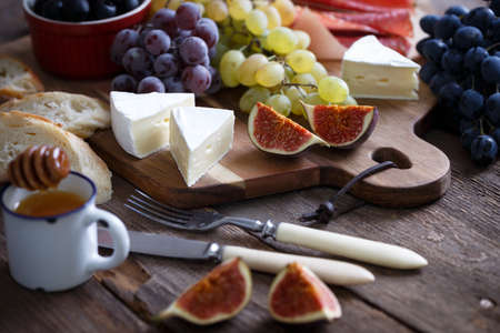 italian breakfast - grapes, brie cheese, salami, figs and olives