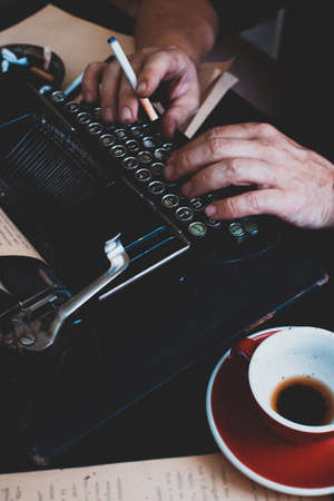 a beautiful old retro typewriter close-up, hands and a cup of coffee