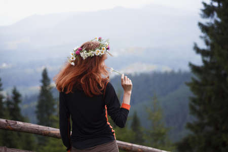 girl in a wreath of wildflowers in the mountains