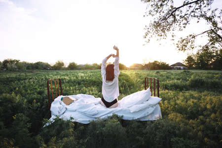 girl resting in the bed in a green field. healthy sleep in nature. Ecotourism Standard-Bild