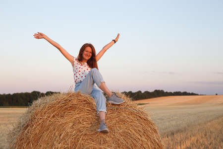 beautiful landscape - round bales and happy girl in the field