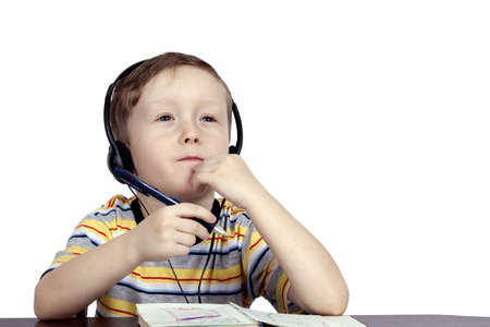a little boy thinks the headphones with a microphone on a light background Stock Photo - 12932312