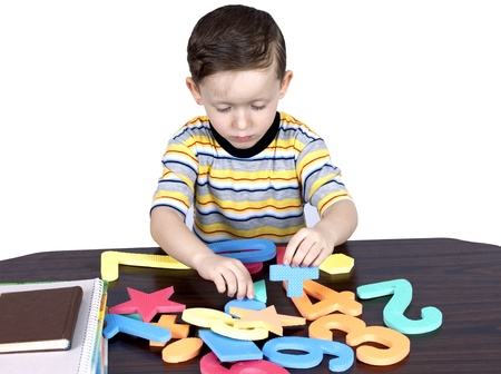a little boy learns the numbers sitting at a table on a white background photo