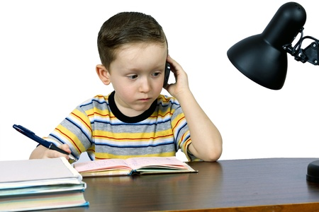 LITTLE BOY SPEAKS ON THE PHONE AT THE OFFICE FOR THE TABLE photo
