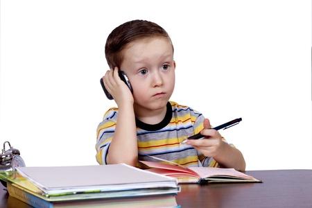 un niño pequeño en la oficina con el teléfono en la mano sobre fondo blanco Foto de archivo - 12932313