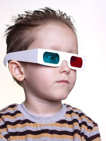 cute little boy sitting in the 3D glasses on a light background photo