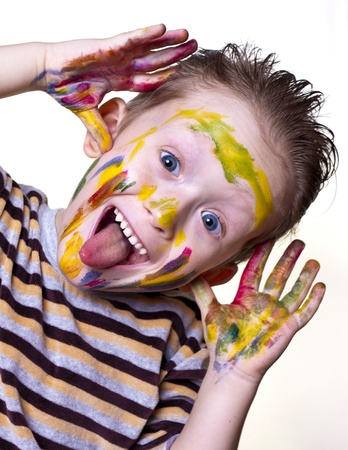 a happy little boy with a cute face smeared paint on a light background photo