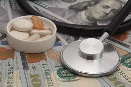 Medical concept - stethoscope and drug over the dollar bills
