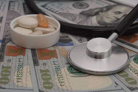 Medical concept - stethoscope and drug over the dollar bills