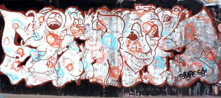 An old brick wall vandalized with graffiti street art. Urban culture abstract background.