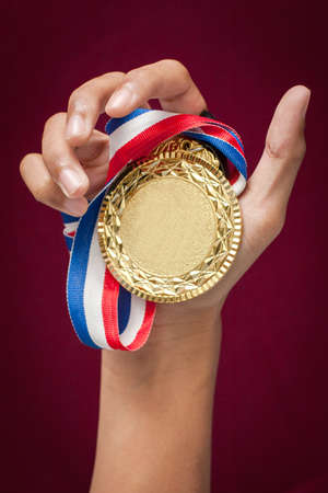 background trophy: hand holding up a gold medal as a winner in a competition Stock Photo