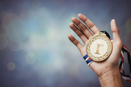trophy winner: hand holding up a gold medal as a winner in a competition Stock Photo