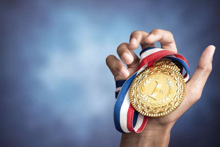 competition success: hand holding up a gold medal as a winner in a competition Stock Photo