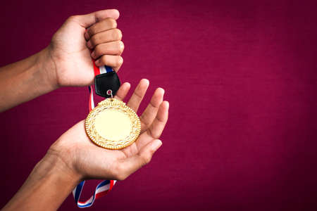 hand holding up a gold medal as a winner in a competition 版權商用圖片