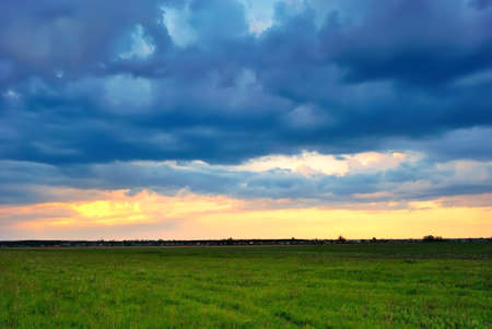 Dramatic sunset over a green field on a summer evening photo