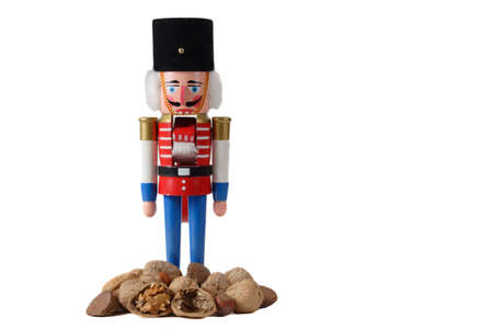 christmas military: Nutcracker soldier,red,blue and black hat  isolated on white background with a pile of nuts.