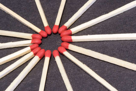 Circle of wood match sticks with a red tips.