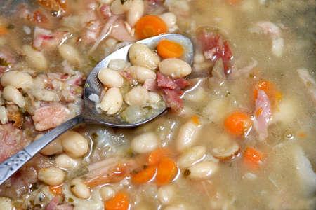 ハムとニンジンと海軍の豆のスープにスプーン。