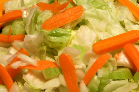 Iceberg green salad with carrots, onions and celery. Фото со стока