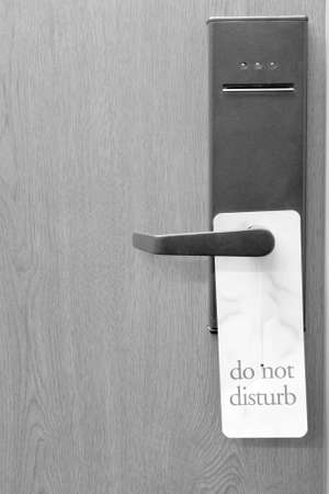 Hotel wood door with a Do not disturb sign hanging on it. black and white,