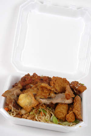 Chinese Buffet food loaded in a to go container with egg roll, noodles, rice, chicken and beef. Stock Photo