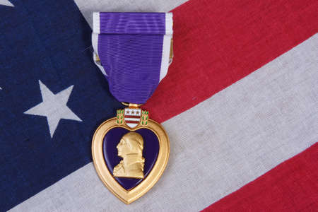 war and military: American Purple Heart Medal on a USA red white and blue  Flag Background.