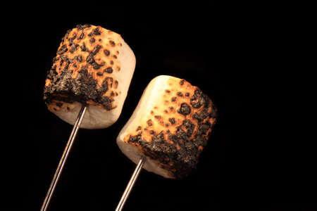 Two roasted marshmallow on a campfire fork with a black background.  Stok Fotoğraf