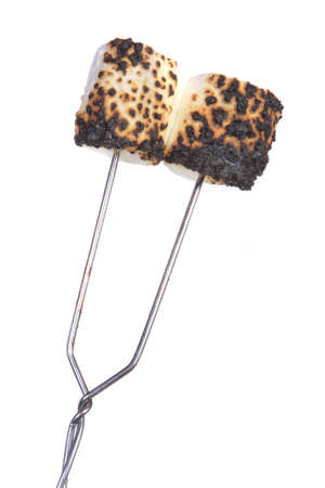 Two roasted marshmallow on a campfire fork with a white background.