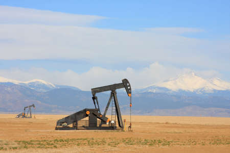 plains: A Pumpjack pumping oil from an oil well in the plains with snow capped mountains in the backgroud.      Stock Photo