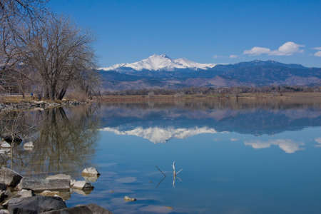 caped: Beautiful scenic landscape Image of Nature reflections in a lake of snow Caped Rocky Mountains and trees. Stock Photo