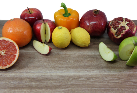 inflammatory: Healthy foods - apples,banana,grapefruit,pomegranate,lemons and pepper on wooden table