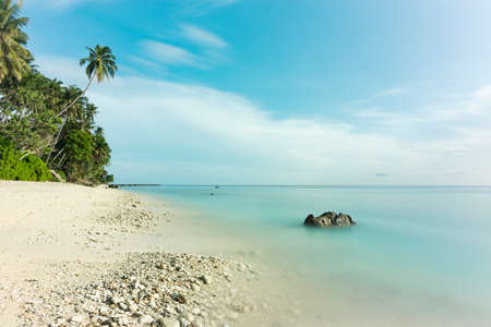 Beautiful view long exposure at the beach, white sand, rock, coconut tree and beautiful blue sky Stockfoto
