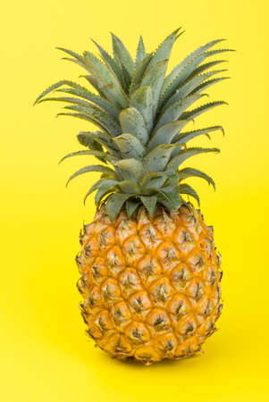 A yellow pineapple isolated on yellow background. Creative tropical fruit concept