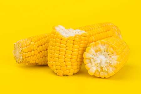 Fresh yellow sweet corn on yellow background