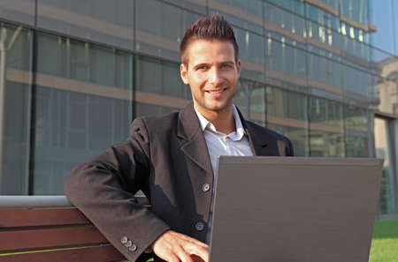 Confident businessman sitting on a bench with a notebook