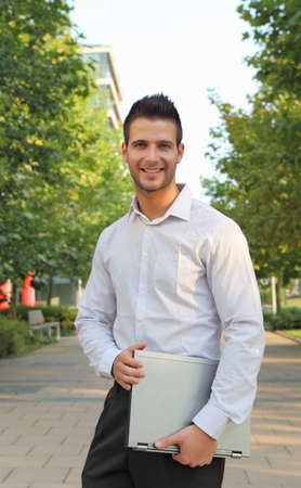 Confident smiling businessman holding a notebook in a park Stock Photo