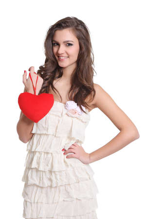 Beautiful brunette girl with a heart sign in her hand photo