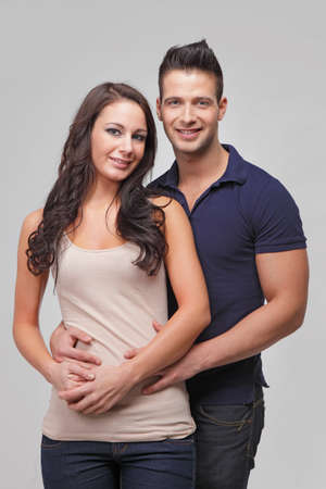 Happy young couple smiling in studio