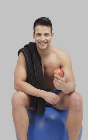 Young adult male sitting on a fitness ball with an apple Stock Photo