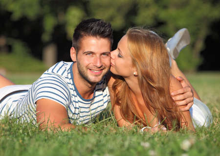 young couple smiling: Happy girlfriend kissing her friend outdoor Stock Photo