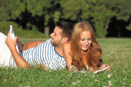 Happy couple reading books outdoor Stock Photo