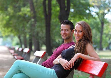 banc de parc: Cute girl souriante à côté de son petit ami sur un banc