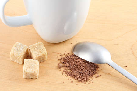 Cacao powder and sugar next to a cup and a spoon Stock Photo